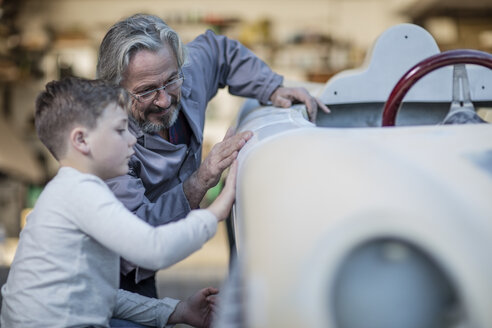 Senior man and boy examining old car together - ZEF009697