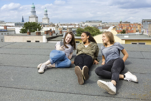 Germany, Berlin, three teenage girls sitting on roof top listening music with earphones - OJF000145