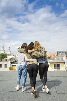 Germany, Berlin, back view of three teenage girls standing arm in arm on roof top - OJF000148