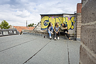 Three teenage girls sitting together on roof top - OJF000151