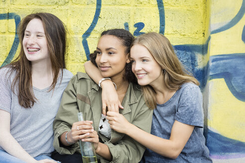 Three teenage girls sitting in front of graffiti - OJF000154