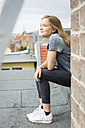 Smiling teenage girl sitting on roof top looking at distance - OJF000157