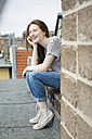 Laughing teenage girl with braces sitting on roof top - OJF000163
