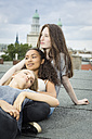 Germany, Berlin, three teenage girls relaxing together on roof top - OJF000166