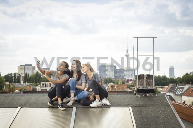 Germany, Berlin, three friends sitting side by side on roof top taking selfie with smartphone - OJF000172 - Julia Otto/Westend61