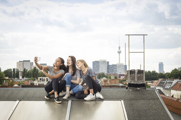 Germany, Berlin, three friends sitting side by side on roof top taking selfie with smartphone - OJF000172