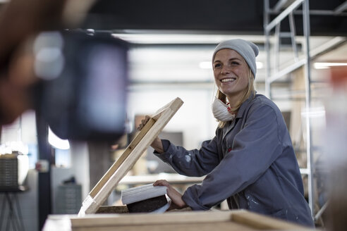 Smiling woman working on frame in workshop - ZEF009758