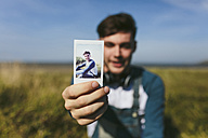 Young man showing polaroid of himself - BOYF000538