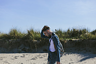 Young man walking on the beach - BOYF000550