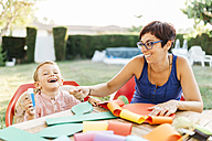 Mother and son doing handicrafts at garden table - JRFF000842