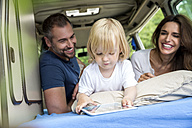 Happy family in van with toddler using tablet - FMKF002782