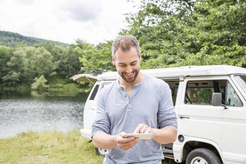 Smiling man using cell phone at a van at lakeside - FMKF002794