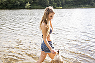 Young woman with her dog in a lake - FMKF002800
