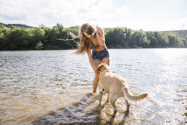Young woman with her dog in a lake - FMKF002806