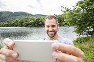 Smiling man taking a selfie at lakeside - FMKF002809