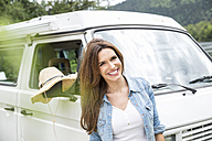 Portrait of happy woman beside van - FMKF002821