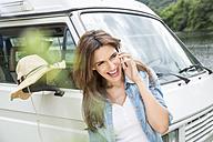 Happy woman on cell phone beside van - FMKF002824