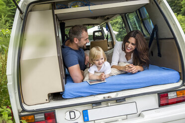 Happy family lying on mattress in van - FMKF002839