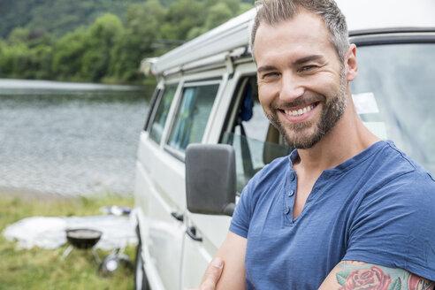 Portrait of smiling man at van at lakeside - FMKF002851