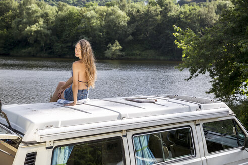 Young woman sitting on roof of a van at lakeside - FMKF002857
