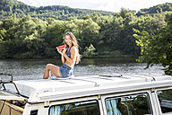 Young woman sitting on roof of a van at lakeside holding slice of watermelon - FMKF002860