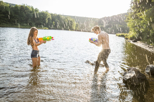 Young couple in a lake splashing with waterguns - FMKF002875
