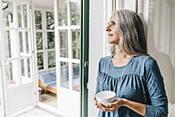 Woman leaning at door frame of her winter garden with cup - KNSF000248