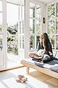 Woman sitting on lounge in winter garden reading book - KNSF000251