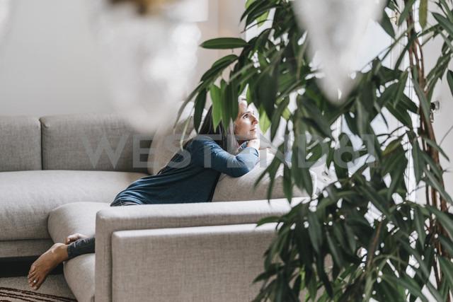 Woman sitting on the couch looking through window - KNSF000260 - Kniel Synnatzschke/Westend61