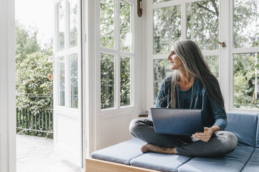 Woman with laptop sitting on lounge in winter garden looking through opened terrace door - KNSF000269