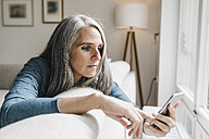 Woman sitting on the couch looking at cell phone - KNSF000275