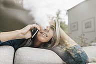 Woman on the phone sitting behind windowpane on the couch looking at distance - KNSF000278