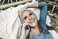 Portrait of laughing woman on the phone lying in hammock - KNSF000281