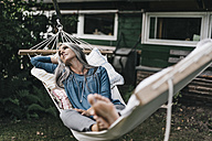 Pensive woman lying in hammock in the garden - KNSF000284