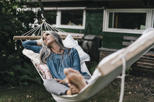 Pensive woman lying in hammock in the garden - KNSF000284