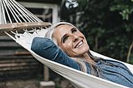 Portrait of smiling woman lying in hammock in the garden - KNSF000287
