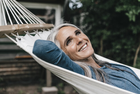 Portrait of smiling woman lying in hammock in the garden - KNSF000287