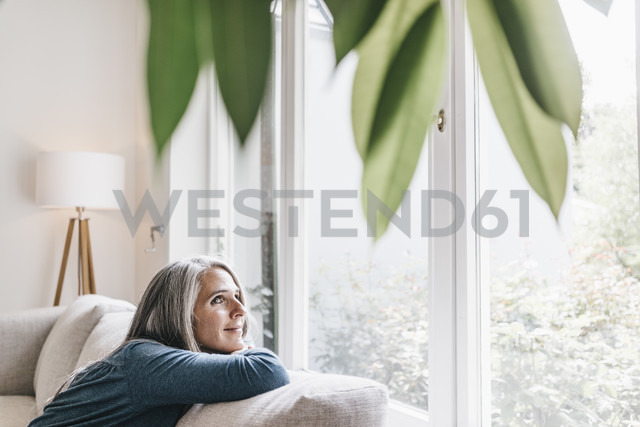 Smiling woman relaxing on the couch at home - KNSF000290 - Kniel Synnatzschke/Westend61
