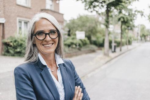 Portrait of smiling businesswoman wearing glasses - KNSF000305