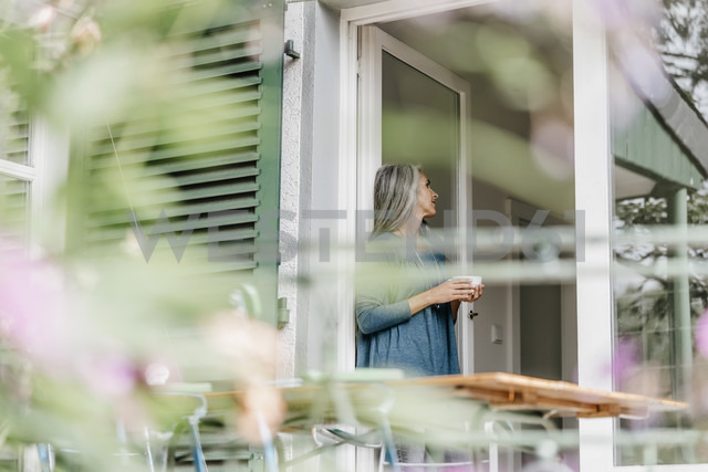 Woman leaning at terrace door with cup of coffee - KNSF000311 - Kniel Synnatzschke/Westend61