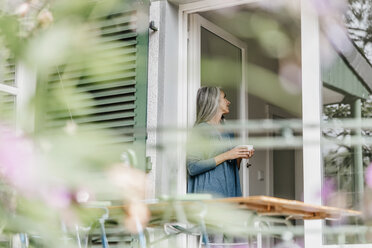 Woman leaning at terrace door with cup of coffee - KNSF000311