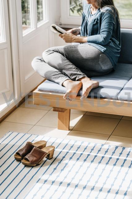 Woman sitting on lounge in winter garden reading book - KNSF000317 - Kniel Synnatzschke/Westend61