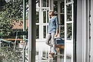 Woman standing at opened terrace door enjoying sunlight - KNSF000320