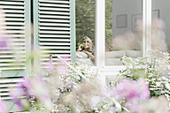 Woman on the phone sitting on the couch looking through window - KNSF000332