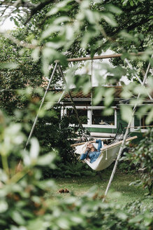 Woman on the phone relaxing in hammock in the garden - KNSF000335