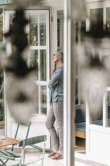 Woman leaning at door frame of her winter garden - KNSF000338