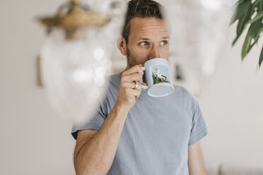 Man drinking coffee at home - KNSF000341