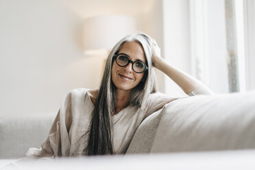 Portrait of smiling woman with long grey hair sitting on the couch - KNSF000347