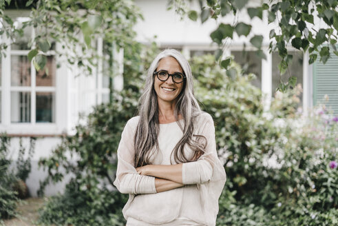 Portrait of smiling woman with long grey hair wearing spectacles standing in the garden - KNSF000356