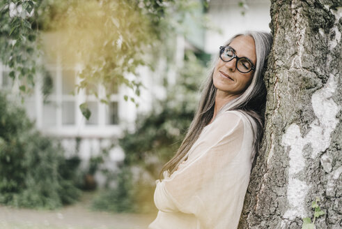 Portrait of woman with eyes closed leaning against tree trunk - KNSF000359